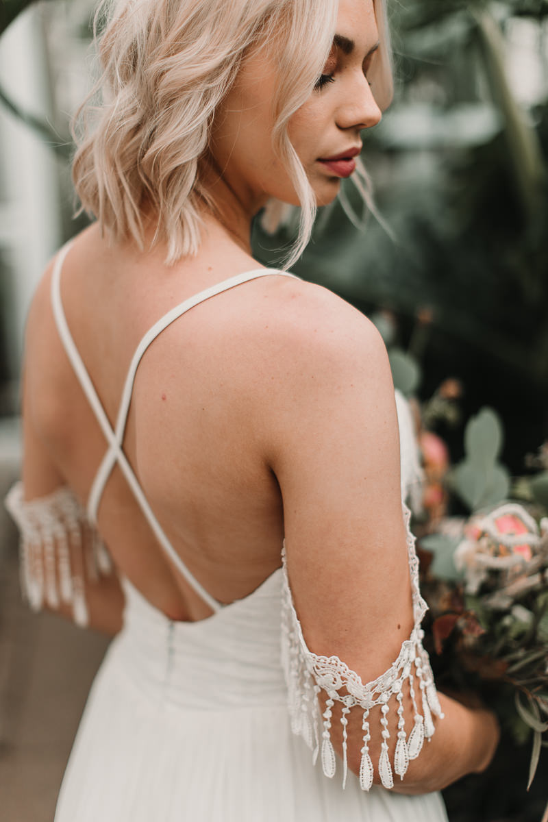 Cross back dress from Shikoba Bride with stunning tassel details. Blush and green Bohemian Wedding Inspiration bringing a little California to you where ever you are in the world. Relaxed styling and desert inspiration and vibes. Wedding ideas for boho brides who an effortlessly relaxed, bohemian wedding. Shot by Natalie Pluck Photography. See full blog post for credits and more inspiration here https://www.nataliepluck.com/bohemian-wedding-inspiration/ 