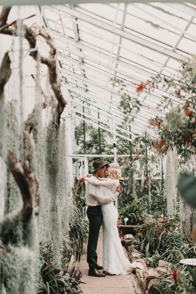 Wedding dress with tassels in a palm house is the perfect inspiration for all you Boho babes out there. Blush and green Bohemian Wedding Inspiration bringing a little California to you where ever you are in the world. Relaxed styling and desert inspiration and vibes. Wedding ideas for boho brides who an effortlessly relaxed, bohemian wedding. Shot by Natalie Pluck Photography. See full blog post for credits and more inspiration here https://www.nataliepluck.com/bohemian-wedding-inspiration/ 