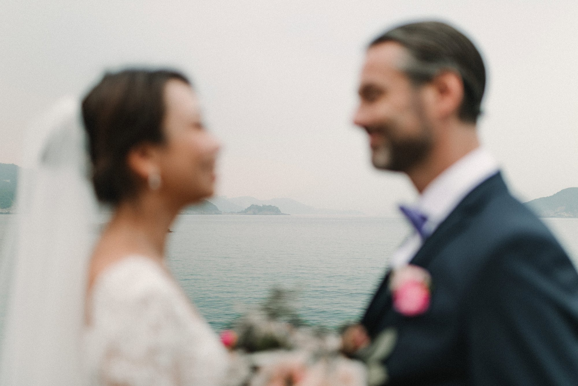 Hong Kong Wedding Photographer Natalie Pluck captures the beautiful wedding of Veronica and Steve. Lace wedding dress with plunging illusion neckline and detachable train. Festoon lighting for a romantic evening reception by candlelight. Fine art Wedding Photography dream wedding inspiration. Wedding reception at one thirty-one in Sai Kung. Unique portraits by lobster bay on the rocks by the sea. Navy suit and purple bow tie for this relaxed groom. Timeless wedding style, chic up do. Pink bouquet inspiration. Photographed by Natalie Pluck. To see more of this wedding click the link: https://www.nataliepluck.com/hong-kong-wedding-photographer #hongkongweddingphotographer #saikungweddingphotographer #hongkongwedding #veronicalamwedding #saikungwedding #onethirtyone #timelessweddinginspiration #kowloonwedding #hkwedding #bertaweddingdress #bertawedding #detatchabletrain #nataliepluck #dreamweddinggown #weddingdressgoals #relaxedweddingphotography #laidbackweddings